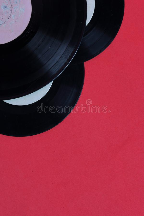 Old vinyl records. Worn and dirty. They lie on the surface of coral color stock photo