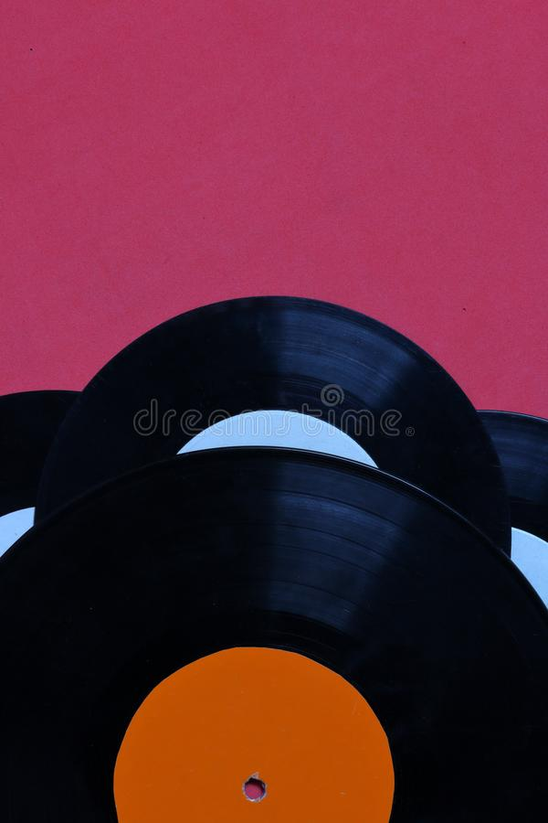 Old vinyl records. Worn and dirty. They lie on the surface of coral color stock image