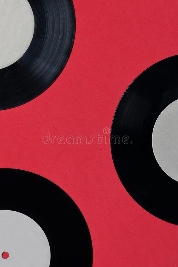 Old vinyl records. Worn and dirty. They lie on the surface of coral color stock images