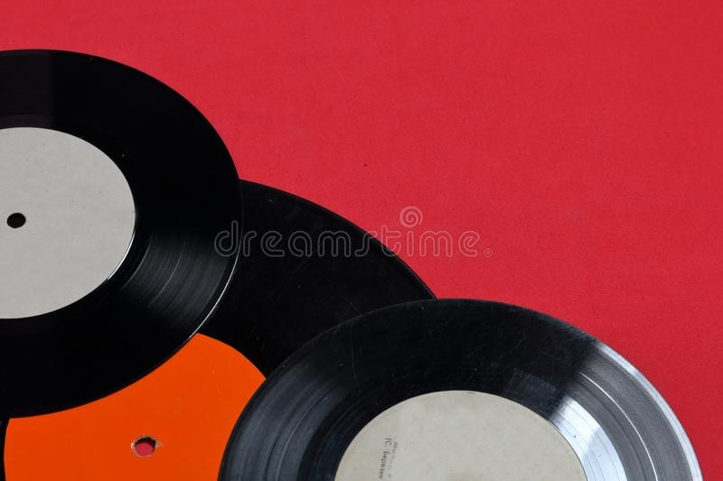 Old vinyl records. Worn and dirty. They lie on the surface of coral color royalty free stock photo