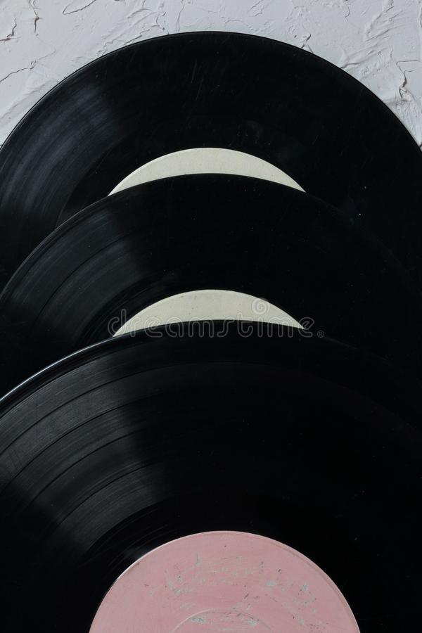 Old vinyl records. Worn and dirty. They lie on the surface covered with decorative plaster stock photography