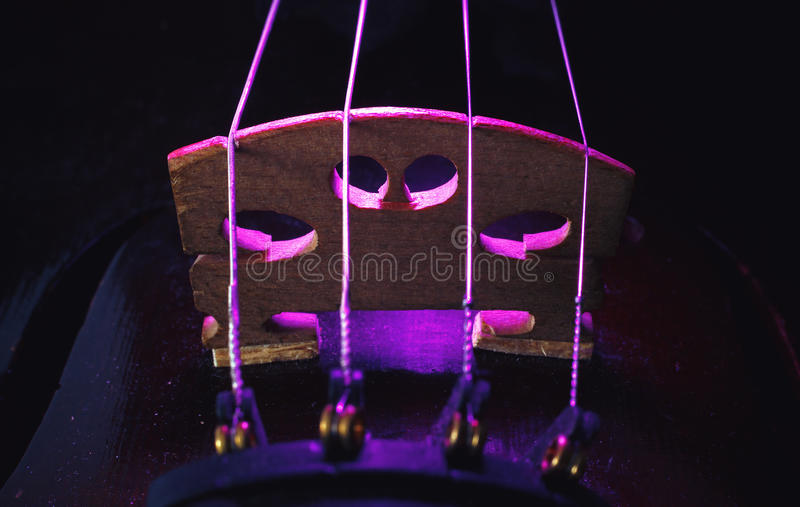 Old Violin Bridge Details. Studio composition of an old dusty violin, blue and purple illumination from aside, closeup view on bridge and strings stock image