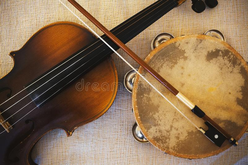 Old Violin From Czechoslovakia and Tambourine. Details of an old and dusty violin from Czechoslovakia and tambourine stock image