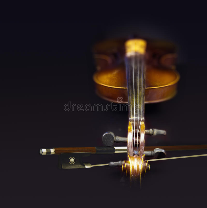 Old violin with fiddlestick. Close view of old violin with fiddlestick in a black background stock photo