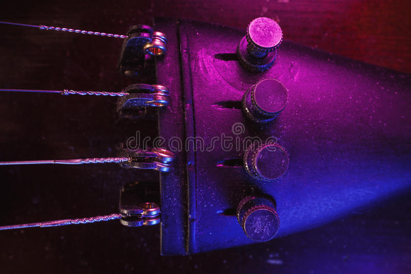 Old Violin Fine Tuners and Strings. Studio composition of an old dusty violin, blue and purple illumination from aside, closeup view on fine tuners and strings royalty free stock image
