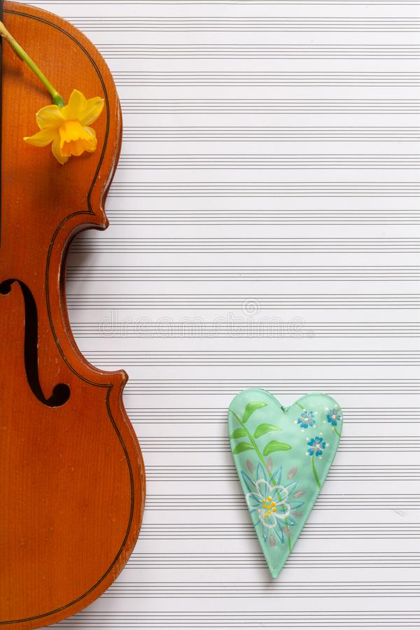 Old violin, narcissus and colorful heart figurine. Top view, close up, flat lay on white music paper background stock images