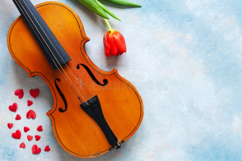 Old violin, red heart figurines and red tulip. Valentine day, 8 March concept. Top view, close-up on blue sky concrete background stock photography