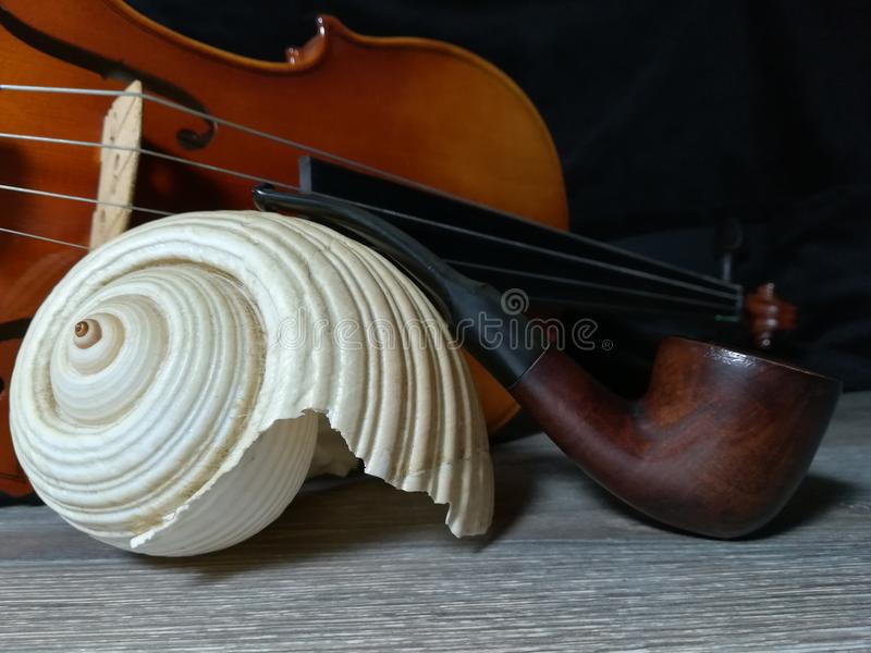 Tobacco pipe, old violin and sea sell royalty free stock image