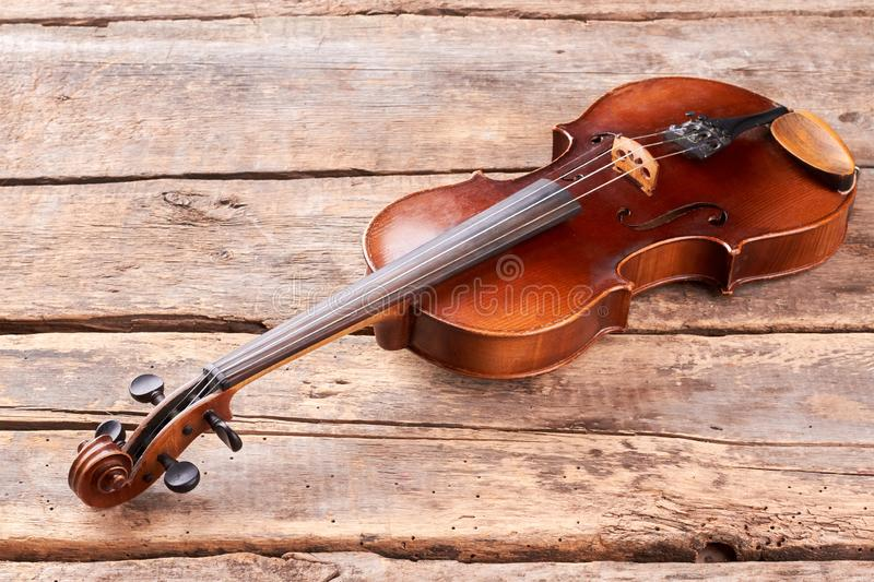 Old violin on wooden floor. Classical stringed instrument of orchestra. Baroque style instrument stock images