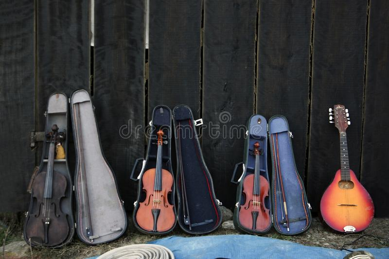 Old violins and a mandolin exposed in front of a black wooden fence. Three violins and a mandolin, three violin cases displayed in front of a black wooed fence royalty free stock image