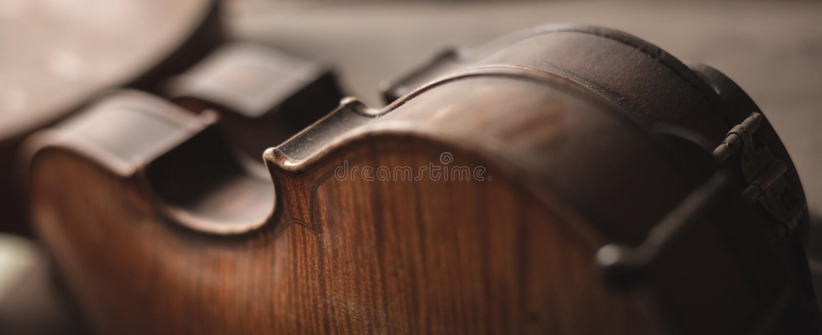 Old violins with a slight layer of dust. Elegant close-up of two antique violins. Dark wooden curves of the instruments covered with a thin layer of dust royalty free stock photo