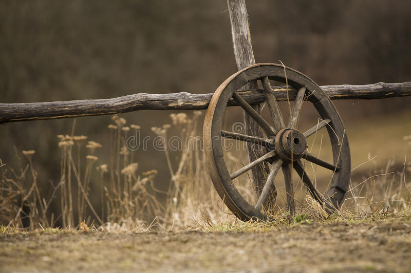 Old wagon wheel. Near the fence royalty free stock image