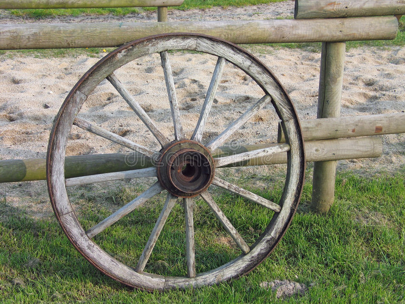 Old wagon wheel. An old wooden wheel of a wagon leans on a ranch fence stock photography