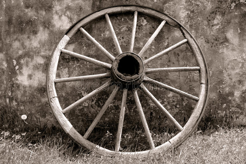 Old Wagon Wheel against an Old Historic House Wall royalty free stock image