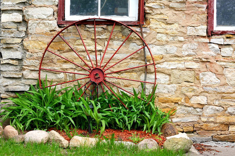 Old Wagon Wheel in Front of Stone Barn stock photos