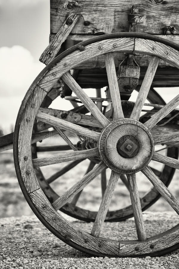 Old wagon wheels. Closeup of the wheels of an old Wagon, Utah, USA. Black and white with slight sepia toning stock photo