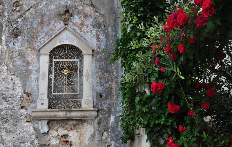 Old wall with altar niche in Croatia. Old wall with altar niche, with red roses on foreground stock image