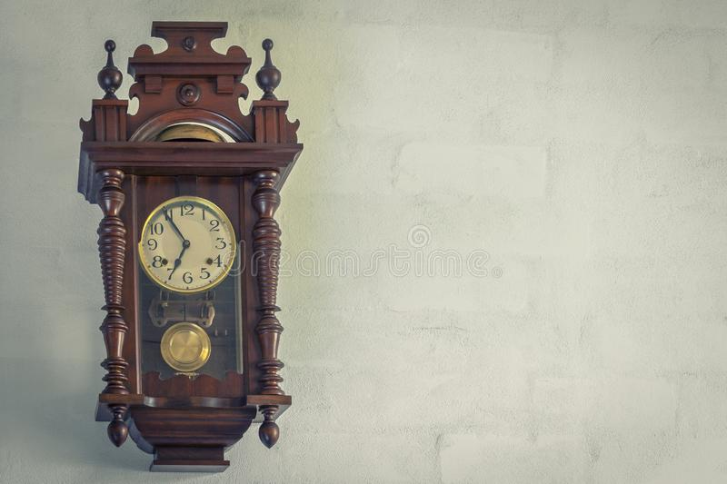 Old wall clock. Old vintage clock hang on a brick wall in the room royalty free stock image