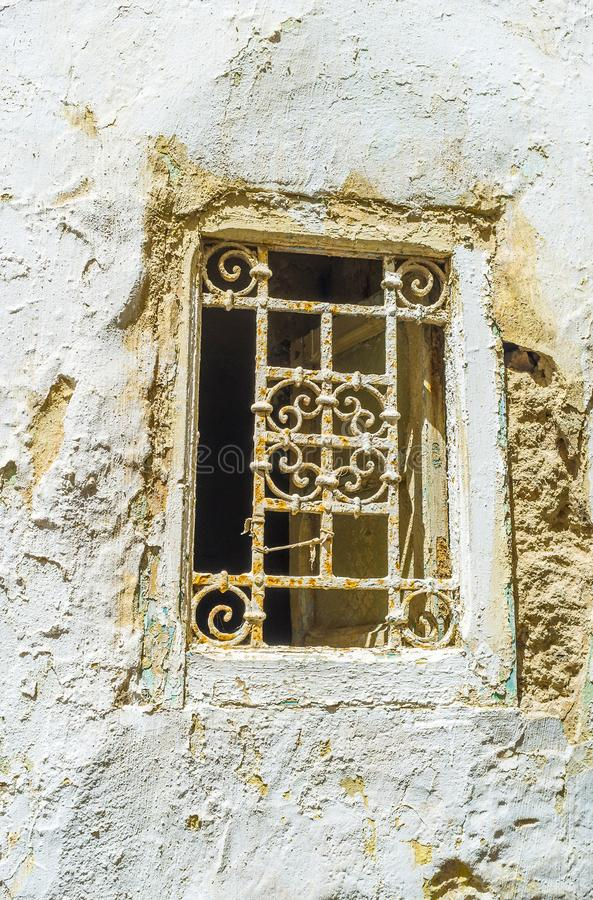 A small window with old grill, Sfax, Tunisia. The old wall with crumbling plaster and rusty grill on tiny window, Sfax, Tunisia stock photography