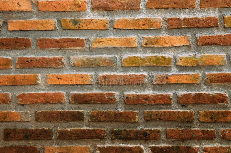 Old wall of dark orange brick. Texture background with grass. Old red brick wall stock photography