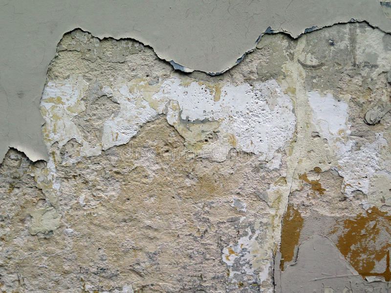 Old wall decrepit. Cement wall with ancient layers of decrepied paints. Detail of the facade of an abandoned house in Paris. Natural light and patina. Paris royalty free stock photography