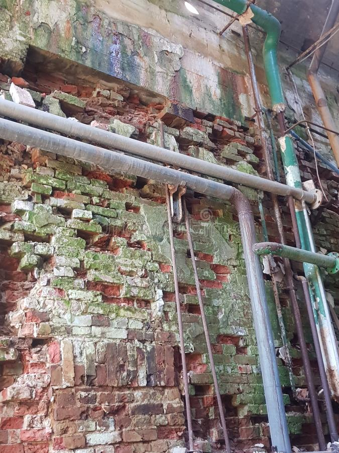 Pipes and an old moss and brick wall royalty free stock photography