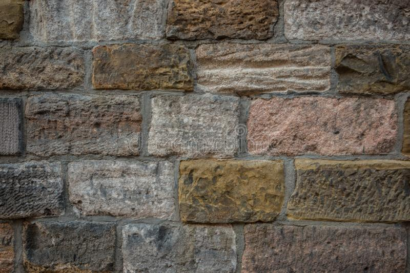 Old wall of a historical building with different colored stones stock images