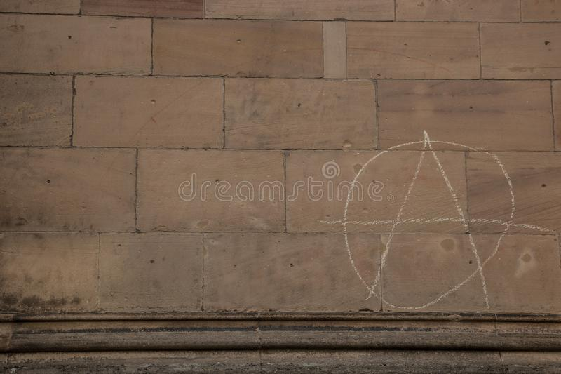 Old wall of a historical building with written anarchy sign stock images