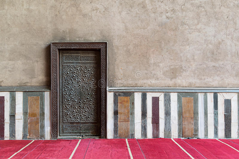 Old wall including a historic decorated bronzed door, Cairo, Egypt. Old wall including a historic decorated bronzed door in an old mosque, Cairo, Egypt royalty free stock photos