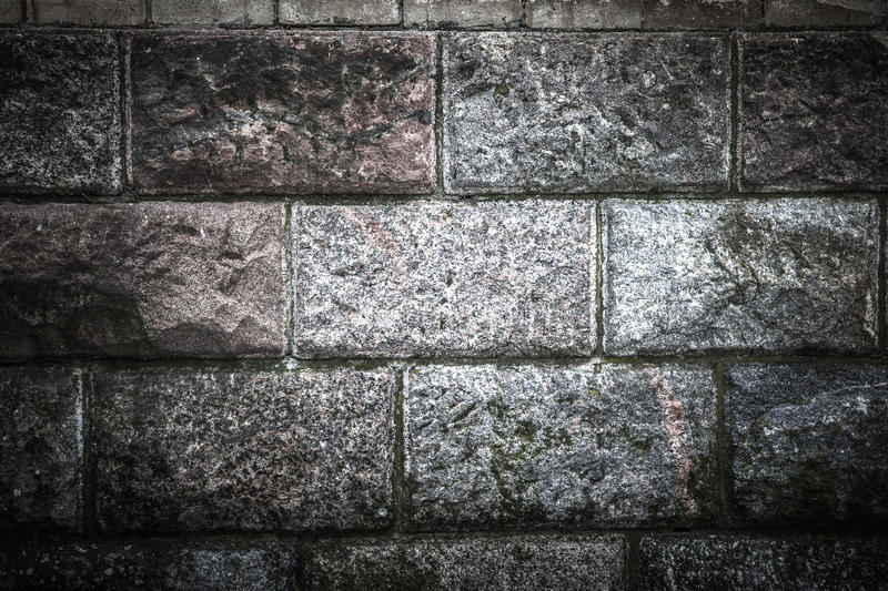 Old wall from marble blocks covered with moss royalty free stock image