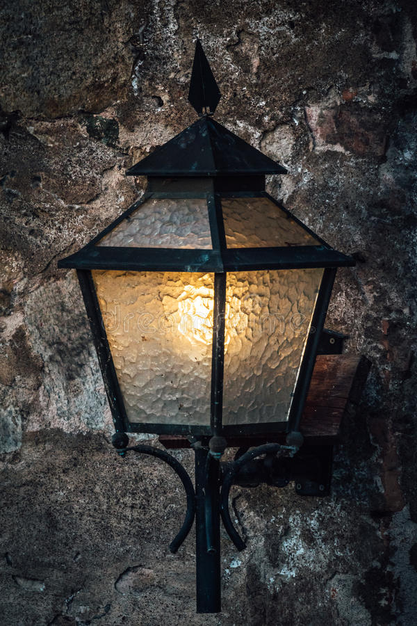 Old wall mounted lamp. Old lamp made of metal and glass mounted on a stone wall royalty free stock image