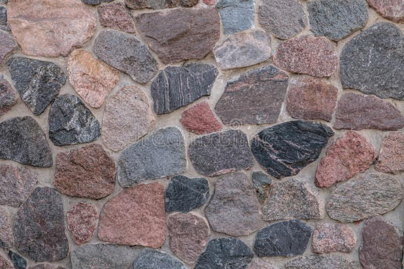 Old wall of a rustic barn made of chipped stone. Fragment. Close-up stock photos