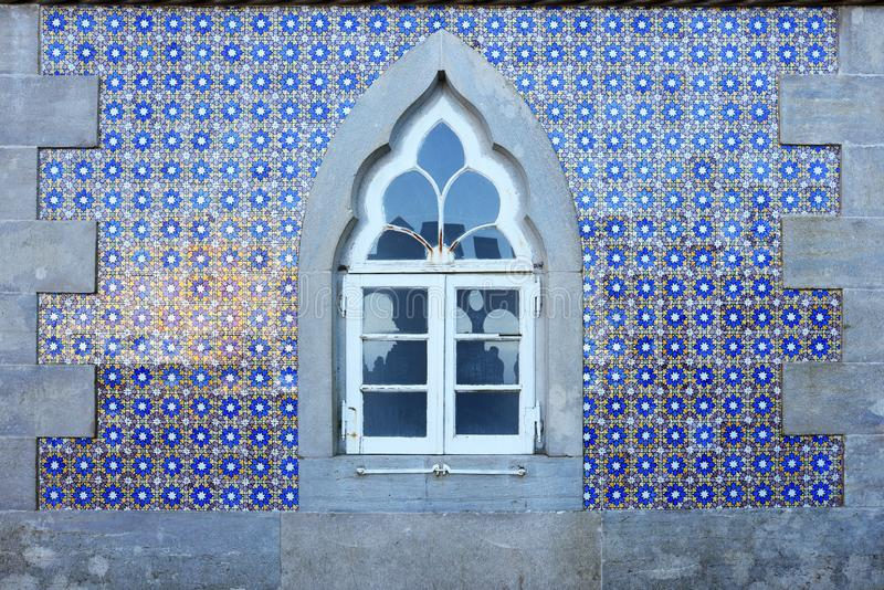 Old wall with traditional Portuguese decor tiles azulezhu in blue,yellow and brown tones with an old window as background. stock photos
