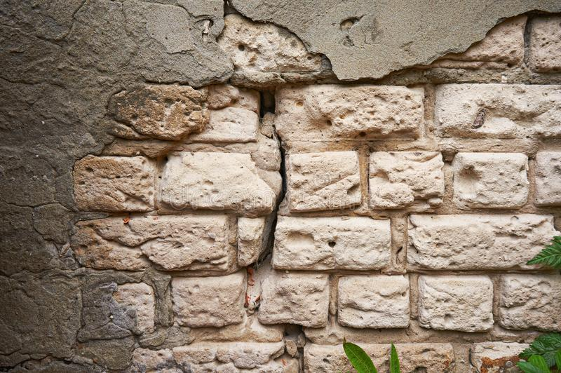 The old wall of white brick with a broken, cracked plaster. Abstract background. royalty free stock photography