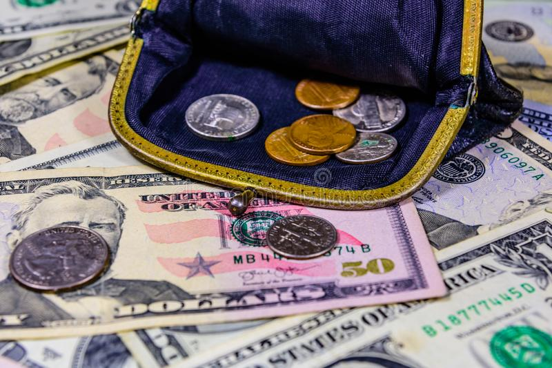 Old wallet with american cent coins over the dollar banknotes. Old wallet with american cent coins over dollar banknotes stock photography
