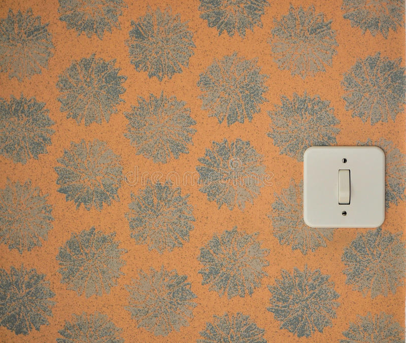 Old wallpaper. White light switch on an old wallpaper stock photos