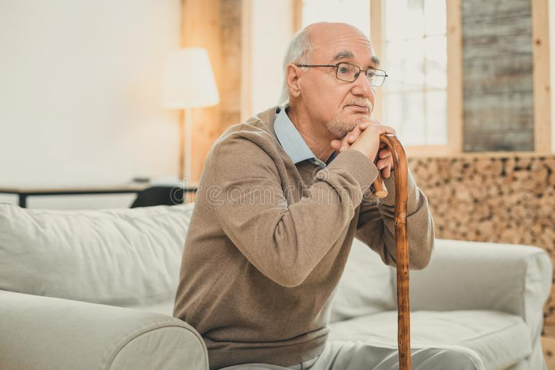 Tired old man with grey hair leaning on the wooden cane. Old ward sitting. Tired old man with grey hair leaning on the wooden cane with bored face and in clear stock photo