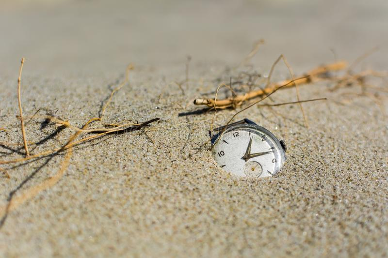 Old watch on the sand. Old men`s watch half buried in the sand - slow life concept stock image