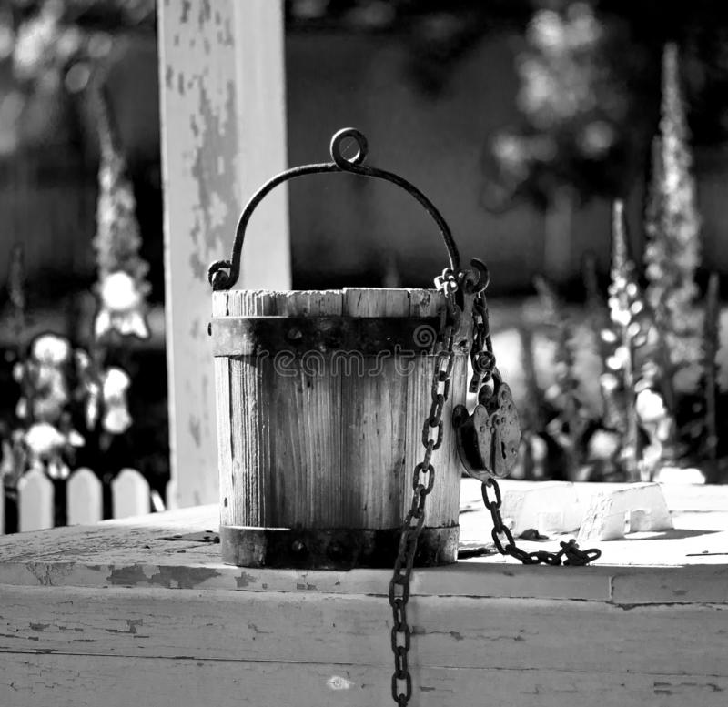 Old water bucket sitting on water well in Williamsburg Virginia. With flowers in background royalty free stock photos