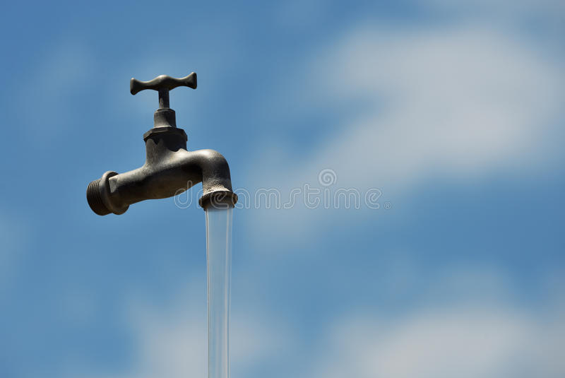 Old water faucet with running water and a blue sky stock images