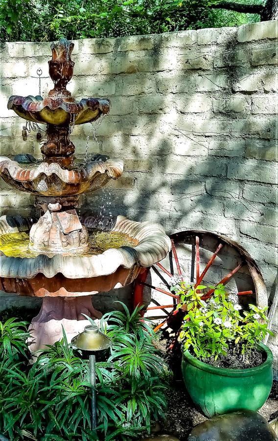 Old water fountain with wagon wheel and flowers surrounding it royalty free stock photo