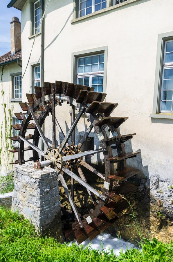 Old water mill wheel next to old building in Schaffhausen Switzerland sunny day royalty free stock photography