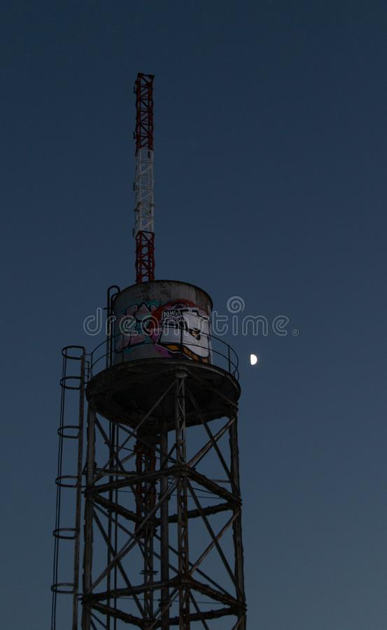Old water tank with antenna and graffiti in front of the moon. At the afternoon royalty free stock photos