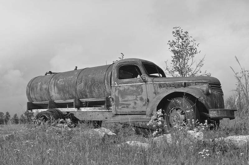 Old water truck (black and white). A very old water truck is left parked in the weeds and brush stock photography