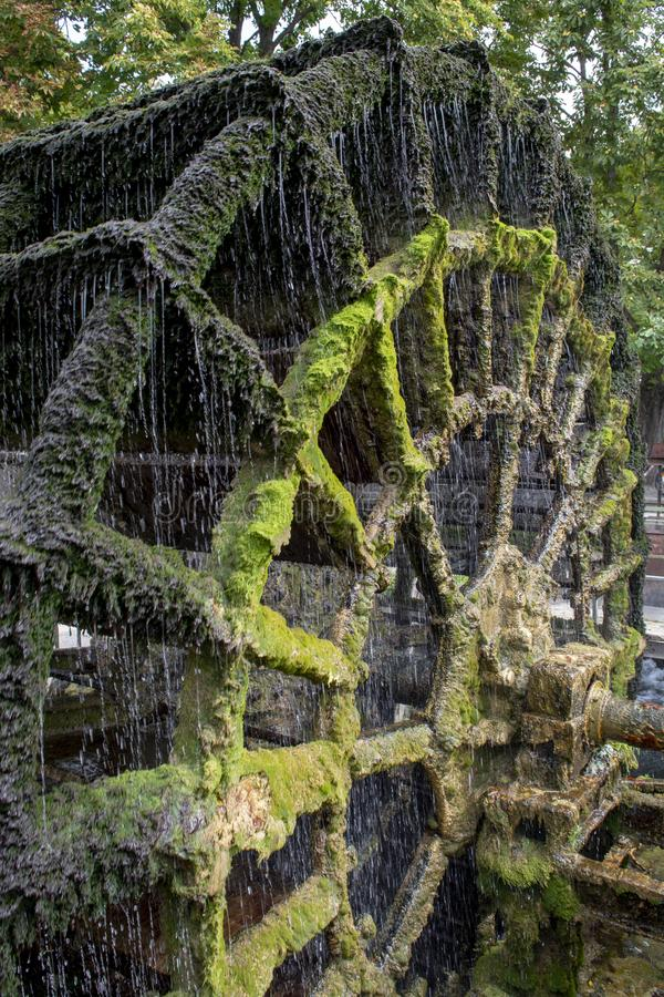 Old waterwheel on river Sorgue in old town Lisle-sul-la-Sorgue in Provence, France, traditional French watermill. Close up stock photo