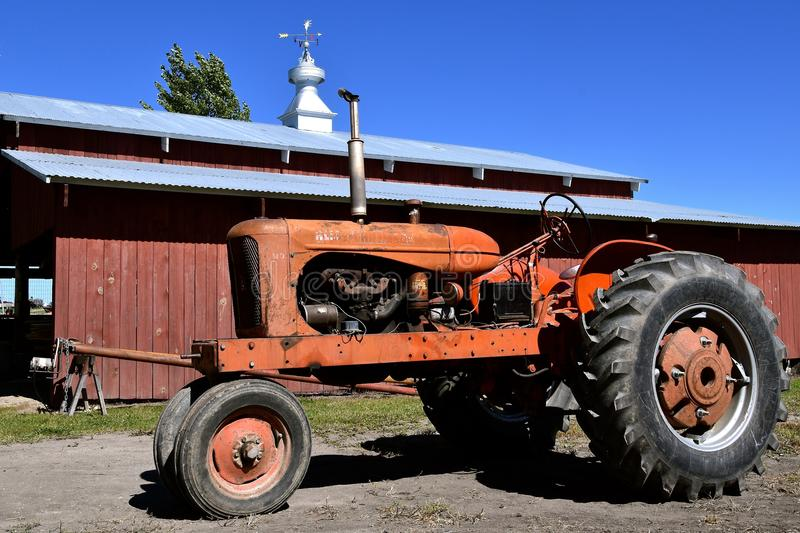Old WD Allis Chalmers tractor. DALTON, MINNESOTA, Sept 8, 2017: An old WD Allis Chalmers tractor with a wood shed in the background is displayed at the annual stock photo