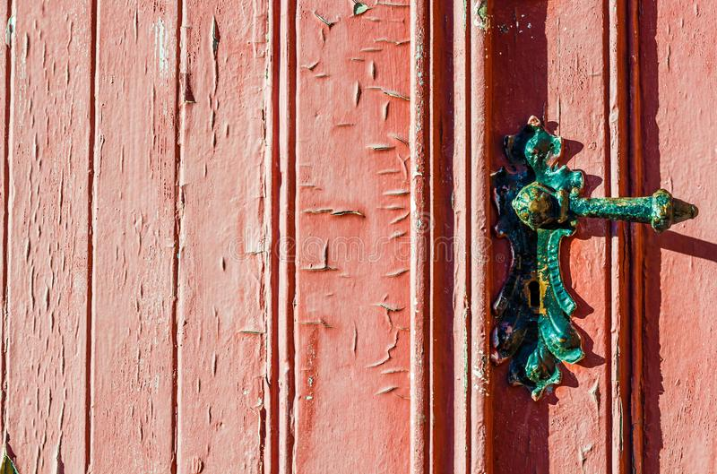 Old weather-beaten red door with old vintage door knob, surface with chapped textured paint. Fragment of old weather-beaten red door with old vintage door knob royalty free stock photos