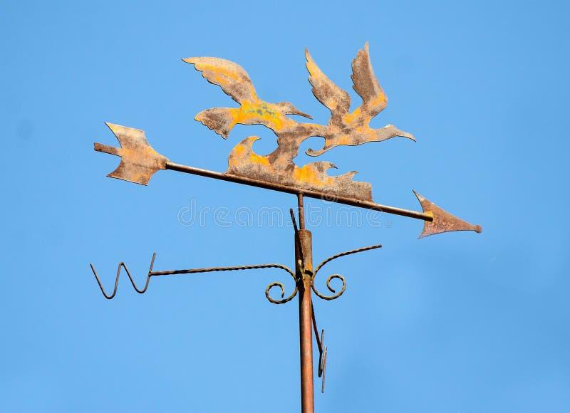Old weather vane. On blue sky background royalty free stock photo