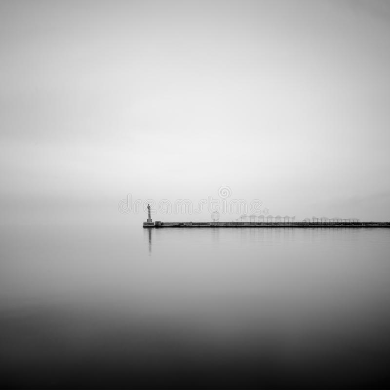 An old weatherd conctere pier in the coastal areas of Creece stock image