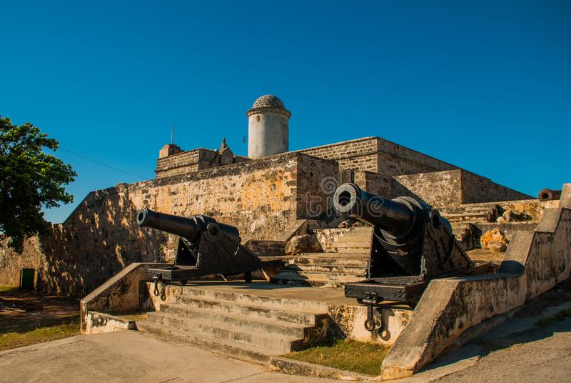 Old weathered cannons and shots exposition near the walls of Jagua fortress Fortaleza de Jagua. Cienfuegos, Cuba. Old weathered cannons and shots exposition stock photography